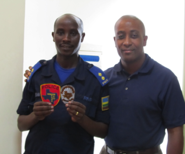 Malcolm presenting patches to Rwanda National Police representative